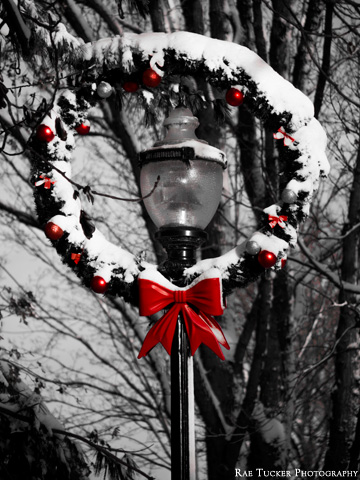 A wreath encircles a lamp post during the holiday season.