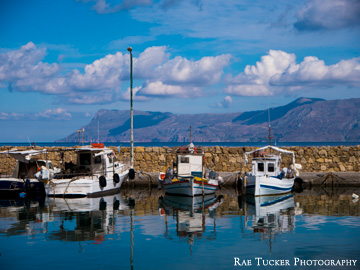 The old fishing port in Kissamos, Greece is lined with fishing boats.