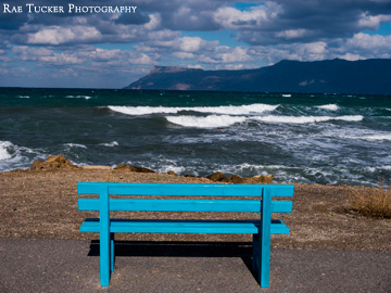 A blue bench provides a place to watch the waves roll in in Kissamos, Greece