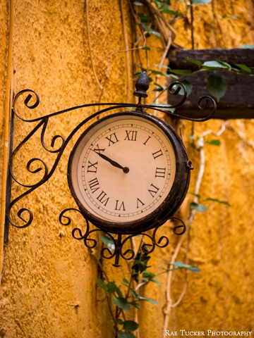 An old-fashioned clock against a yellow wall