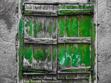 The peeling, green paint of old window shutters stand out against the black and white image.