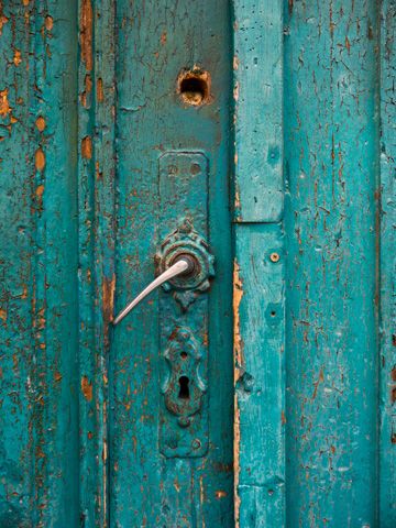 Turquoise paint peels and cracks on this wooden door in Brasov, Romania
