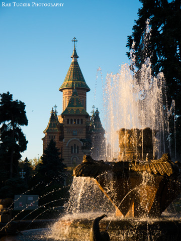 The morning sun illuminates a fountain that stands before the Orthodox cathedral in Timisoara, Romania