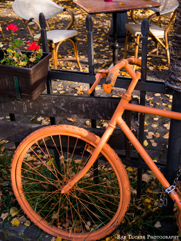 An orange-painted bicycle handles and wheel
