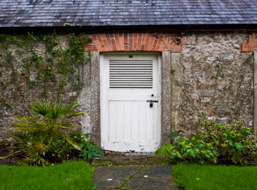 A wooden door of a stone house on the grounds of the Blarney Castle.