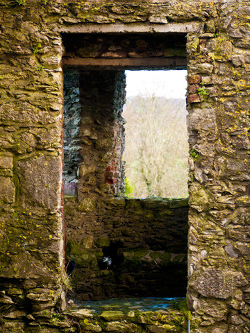 A window in a stone tower of the Blarney Castle during the winter.