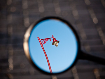 A red lamppost is reflected in a rearview mirror.