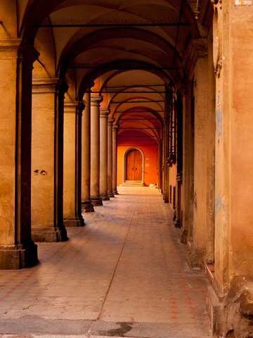 A door stands at the end of this portico in Bologna, Italy.