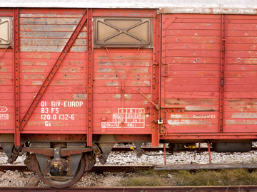 The red, peeling paint and rust of an old train car in Forli, Italy.