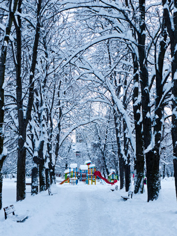 At the end of a snow covered path stands a colorful playground at a park in Sofia, Bulgaria