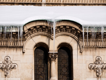 Snow and icicles over a church window