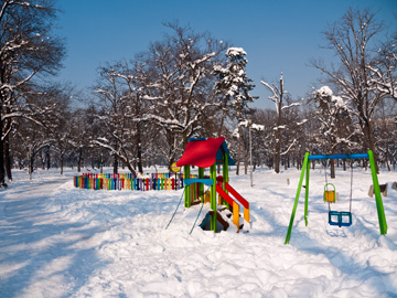 The sun shines over a colorful playground covered in snow in Sofia, Bulgaria