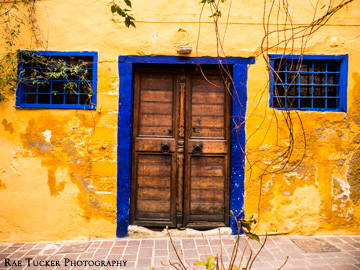 Bold yellows and blues on a wall with double, wooden doors and windows.