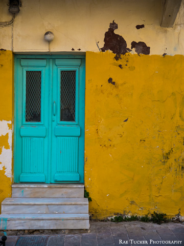 An old wall, painted yellow, offsets a teal-colored entrance.