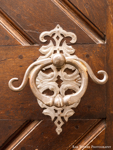 An ornate door knocker on a wooden door.