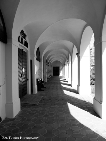 A black and white image of a walkway lining a church courtyard in the South Bohemia region of the Czech Republic.