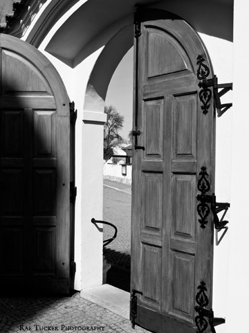 A black and white image of wooden doors that lead to a church courtyard.