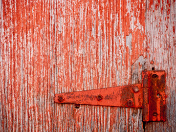 Red, peeling paint with a rusty hinge on a wooden door