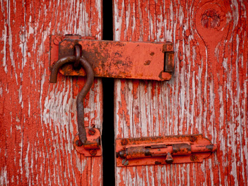 Rusty lock on a door with red peeling paint