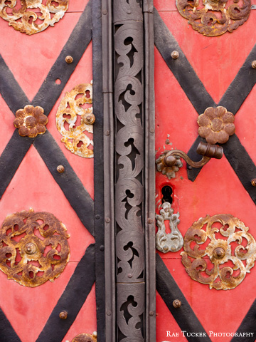 An ornate, red, metal door shows signs of wear and rust.