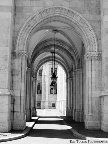 A black and white image of light and shadows filtering through an arched walkway outside of the Hungarian Parliament building in Budapest.