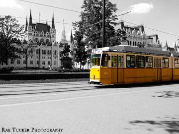 An old-fashioned, yellow tram against a black and white background in Budapest, Hungary