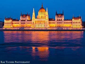 The Hungarian Parliament glows along the Danube river in the early evening in Budapest