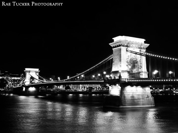 A black and white image of the Chain Bridge and Danube River at night in Budapest, Hungary