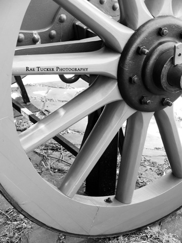 A soft, black and white image of a wagon wheel