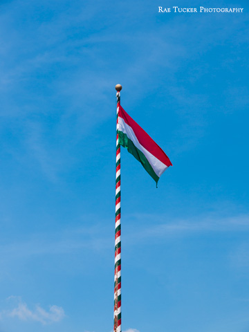 The red, white and green of the Hungarian flag against a blue sky