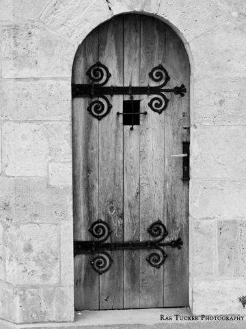 A black and white image of an old, wooden door in Budapest, Hungary