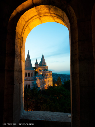 A view of Fisherman's Bastion from a window at dusk in Budapest, Hungary