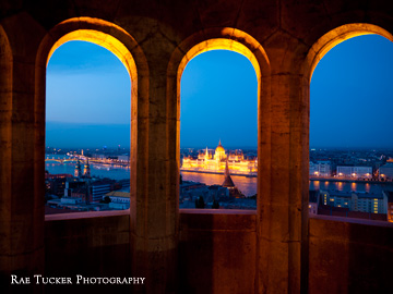 The Hungarian Parliament building, illuminated at night, as seen through the windows of Fisherman's Bastion in Budapest.