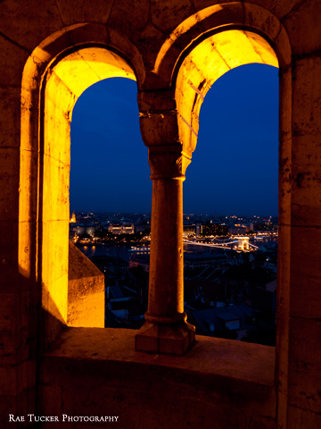 Windows at Fisherman's Bastion look over Budapest and the Chain Bridge in the early evening.