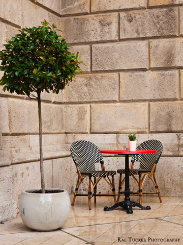 A table and chairs against a stone wall at the Opera Cafe in Budapest, Hungary