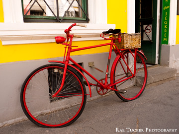 An old-fashioned red bicycle with a wicker basket