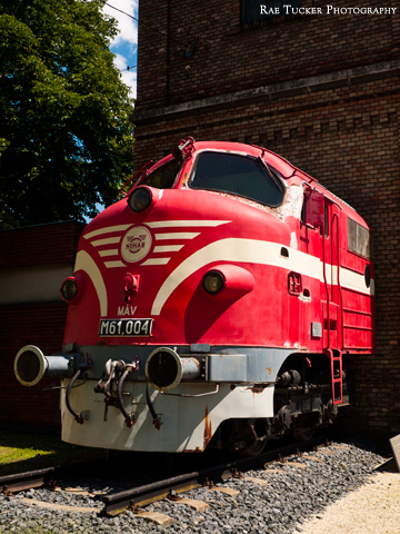 A red train appears to be emerging from a brick building in Tapolca, Hungary