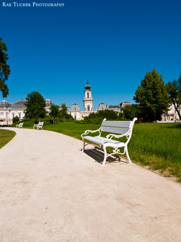 A white park bench on a path leading to the Festetics Palace in Keszthely, Hungary