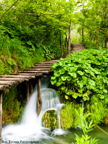 A wooden boardwalk over a waterfall in Croatia.