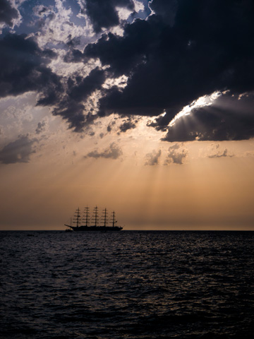 Light from the setting sun shines through storm clouds over a tall ship on the Adriatic Sea