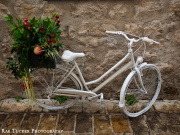 A white bicycle with a basket filled with produce in Budva, Montenegro