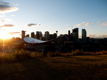 As the sun sets, it illuminates downtown Calgary and the Saddeldome in Alberta, Canada.