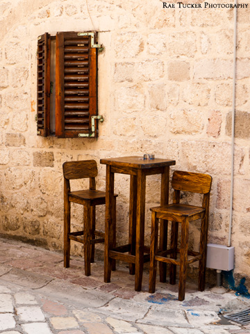 Wooden shutters and a wooden bar table and chairs on a stone street in Kotor, Montenengro