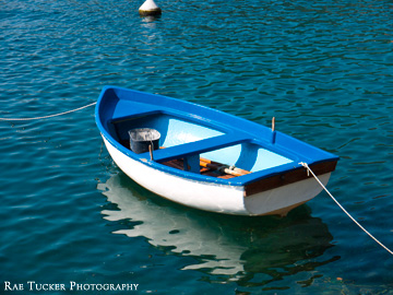 A small blue and white row boat in the Kotor Bay