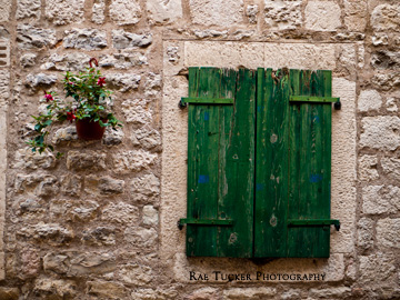 Green, wooden shutters and a small plant adorn a stone wall in Kotor, Montenegro