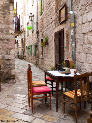 A stone street in Kotor, Montenegro hosts an eclectic patio with wooden chairs and table and a typewriter.