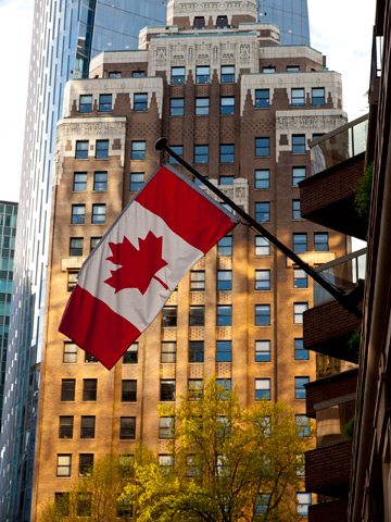 A Canadian flag and the Marine Building in Vancouver, Canada
