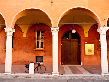 A bicycle parked under a portico in Modena, Italy