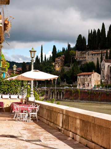 A restaurant patio in Verona overlooks the Adige river