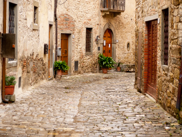 A cobblestone street and stone homes in Montefioralle, Italy